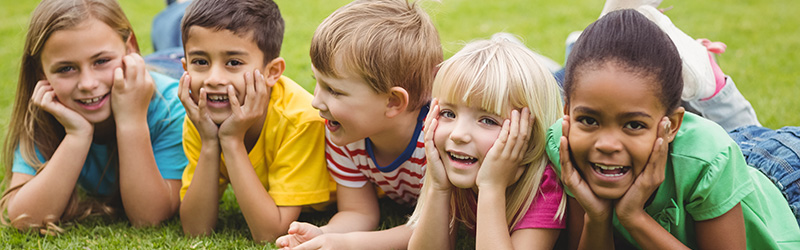 Smiling children lying in a row in grass